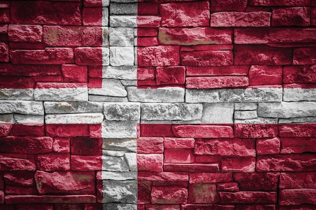 石の壁の背景にデンマークの国旗