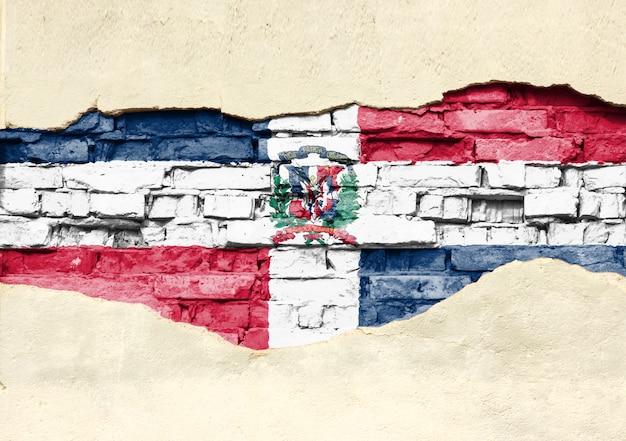 Национальный флаг доминиканской республики на фоне кирпича. кирпичная стена с частично разрушенной штукатуркой, фоном или текстурой.