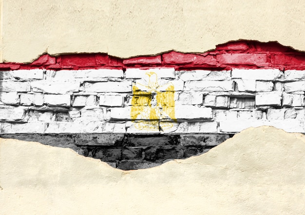 レンガの背景にエジプトの国旗。部分的に破壊された漆喰、背景またはテクスチャのレンガの壁。