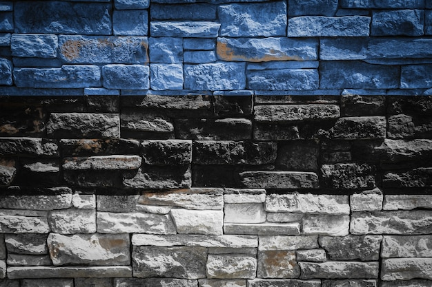 石の壁の背景にエストニアの国旗。