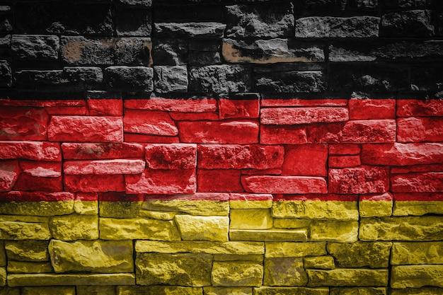 石の壁の背景にドイツの国旗