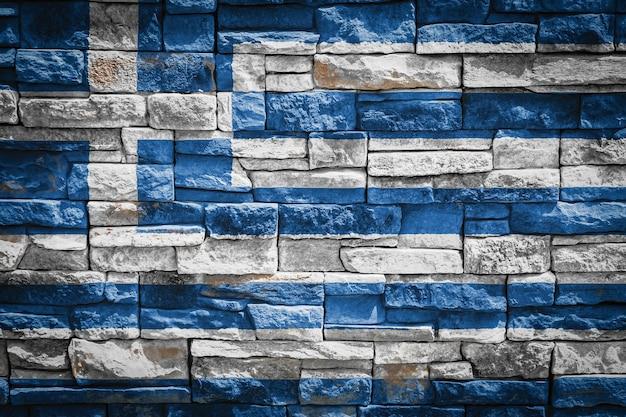 石の壁の背景にギリシャの国旗