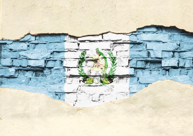 Национальный флаг гватемалы на фоне кирпича. кирпичная стена с частично разрушенной штукатуркой, фоном или текстурой.