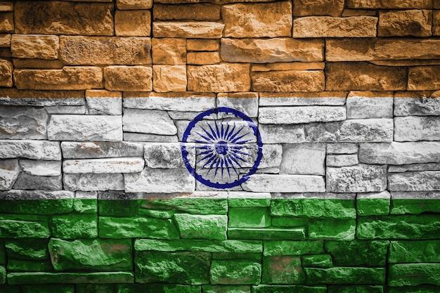 石の壁の背景にインドの国旗