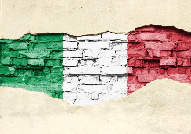 Национальный флаг италии на фоне кирпича. кирпичная стена с частично разрушенной штукатуркой, фоном или текстурой.