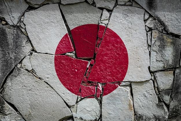 古い石の壁にペンキの色で描かれている日本の国旗