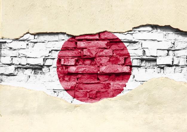 レンガの背景に日本の国旗。部分的に破壊された漆喰、背景またはテクスチャのレンガの壁。