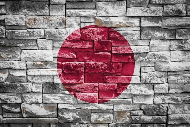 石の壁の背景に日本の国旗