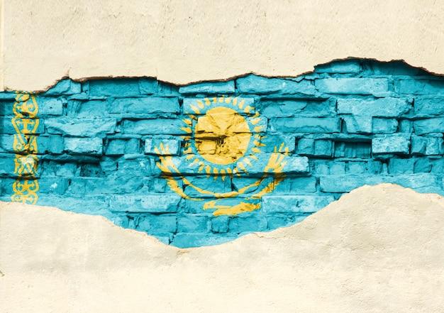 Государственный флаг казахстана на фоне кирпича. кирпичная стена с частично разрушенной штукатуркой, фоном или текстурой.