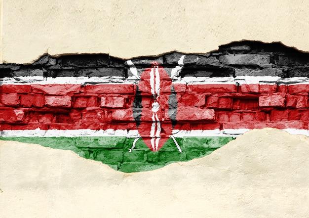 Национальный флаг кении на фоне кирпича. кирпичная стена с частично разрушенной штукатуркой, фоном или текстурой.