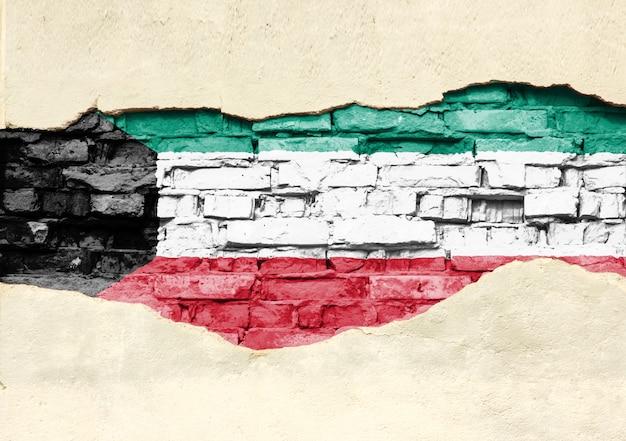 Национальный флаг кувейта на фоне кирпича. кирпичная стена с частично разрушенной штукатуркой, фоном или текстурой.