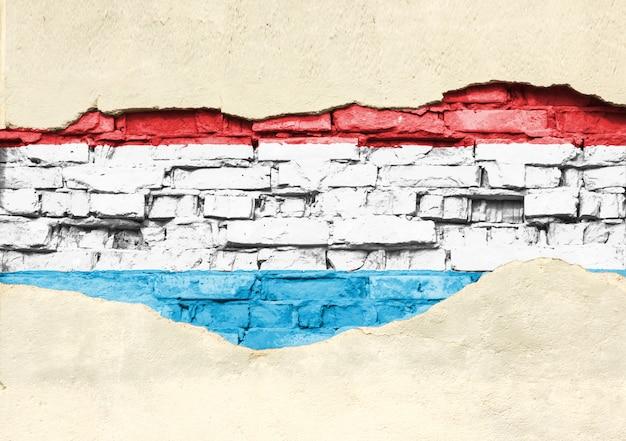 Национальный флаг люксембурга на фоне кирпича. кирпичная стена с частично разрушенной штукатуркой, фоном или текстурой.