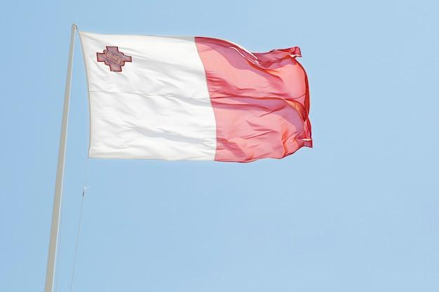 Национальный флаг мальты с голубым небом на фоне