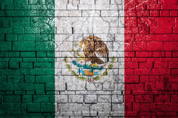 Национальный флаг мексики на фоне кирпичной стены.