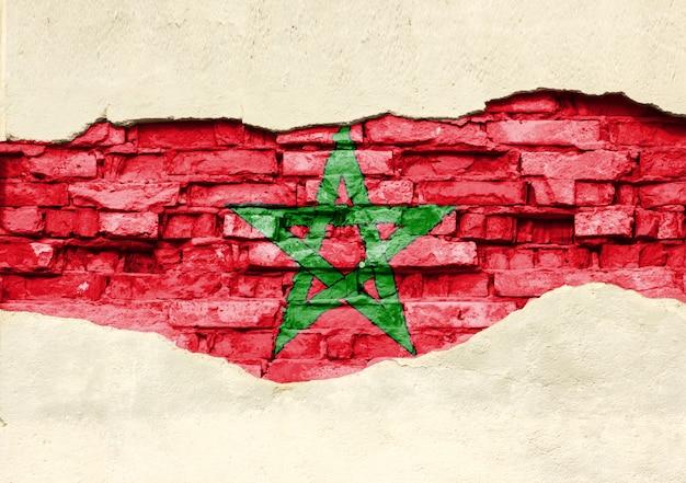 Национальный флаг марокко на фоне кирпича. кирпичная стена с частично разрушенной штукатуркой, фоном или текстурой.