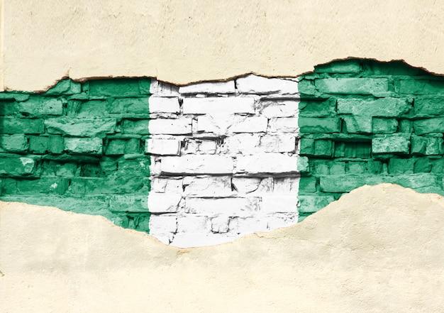 벽돌 배경에 나이지리아의 국기입니다. 부분적으로 파괴 된 석고, 배경 또는 질감 벽돌 벽.