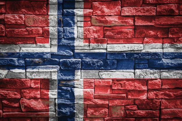 石の壁の背景にノルウェーの国旗