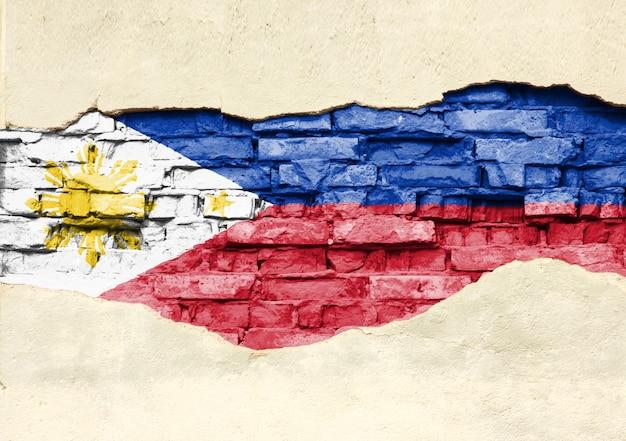 Национальный флаг филиппин на фоне кирпича. кирпичная стена с частично разрушенной штукатуркой, фоном или текстурой.
