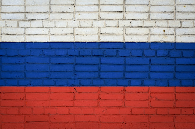古いレンガの壁にペンキの色で描かれているロシアの国旗。レンガの壁の背景にフラグ。