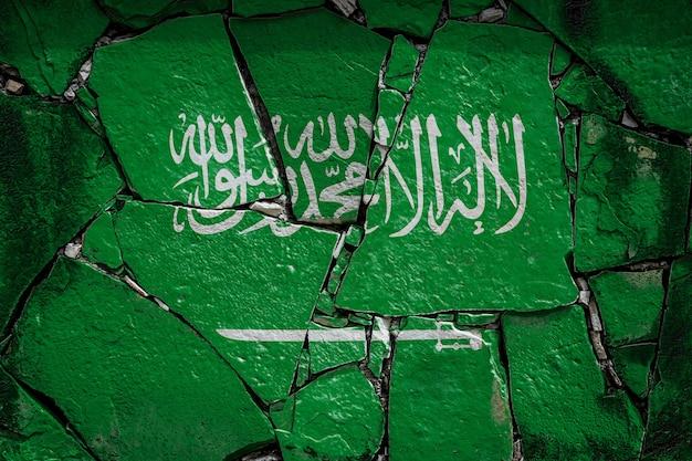 Национальный флаг саудовской аравии, изображающий краской на старой каменной стене. флаг баннер на фоне сломанной стены.