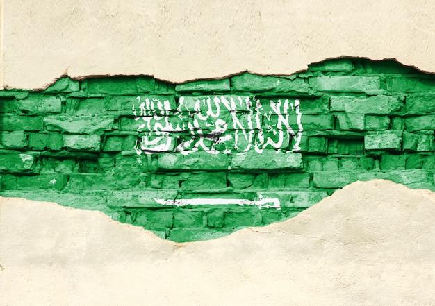 Национальный флаг саудовской аравии на фоне кирпича. кирпичная стена с частично разрушенной штукатуркой, фоном или текстурой.