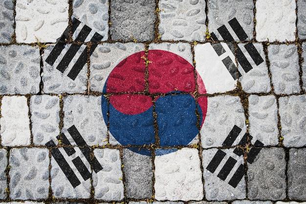 石の壁の背景に韓国の国旗。石のテクスチャの背景にフラグ。