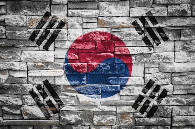 石の壁の背景に韓国の国旗