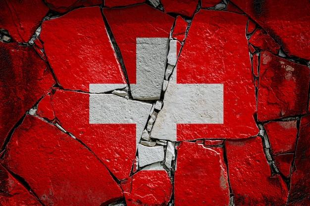 古い石の壁にペンキの色で描かれているスイスの国旗。壊れた壁の背景に旗の旗。