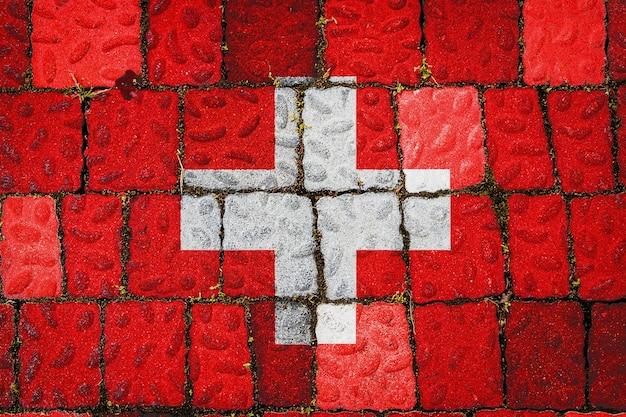 石の壁の背景にスイスの国旗。石のテクスチャの背景にフラグ。