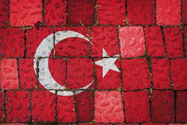 Национальный флаг турции на фоне каменной стены. флаг на фоне текстуры камня.