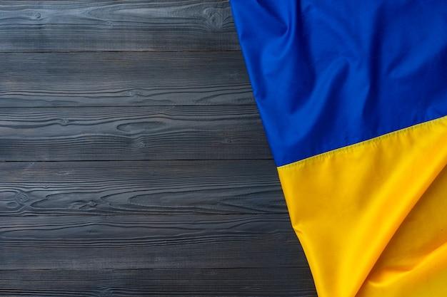 Государственный флаг украины на темном деревянном фоне, копией пространства