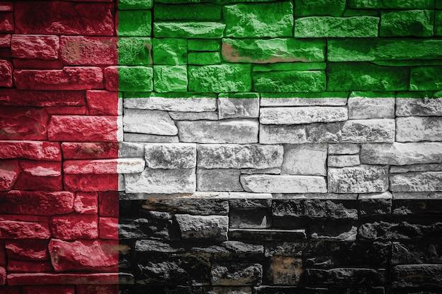 石の壁の背景にアラブ首長国連邦の国旗。