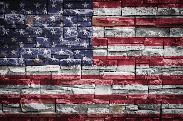 石の壁の背景に米国の国旗