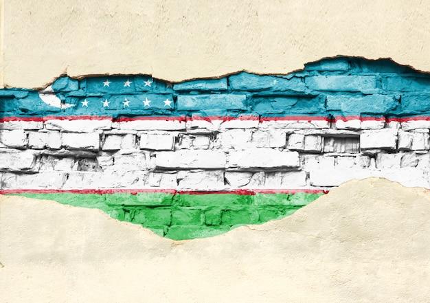 Государственный флаг узбекистана на фоне кирпича. кирпичная стена с частично разрушенной штукатуркой, фоном или текстурой.