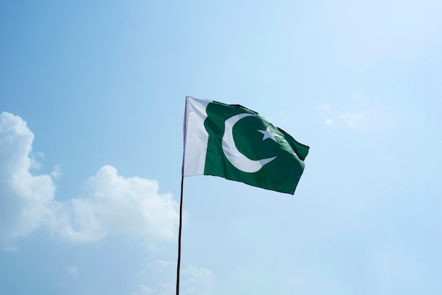 The national flag of pakistan flying in the blue sky with clouds