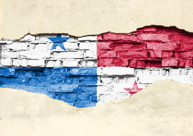 National flag of panama on a brick background. brick wall with partially destroyed plaster, background or texture.