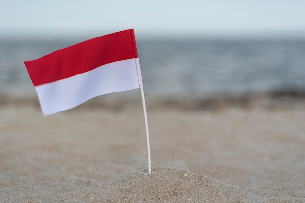 National flag of poland on the beach. sea on surface. red and white flag.