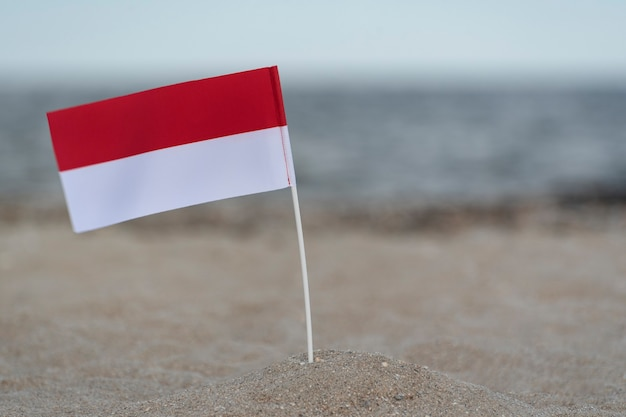 National flag of poland on sandy shore. red and white flag.