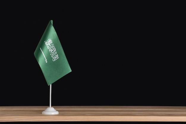 National flag of saudi arabia on table, black background