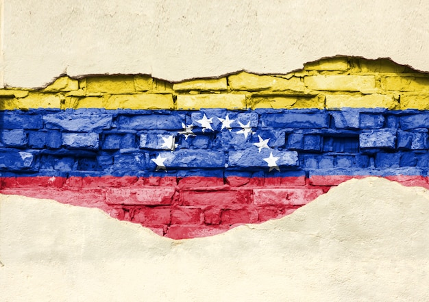 National flag of venezuela on a brick background. brick wall with partially destroyed plaster, background or texture.