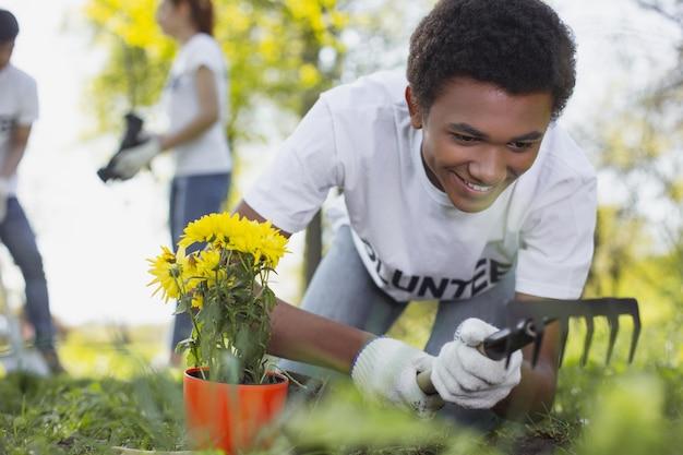 국립 정원. 정원 도구를 사용하는 동안 웃 고 활기찬 남성 자원 봉사자