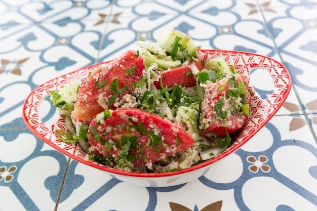 Национальный грузинский салат из свежих овощей, помидоров и зелени, лука и кинзы. фото высокого качества