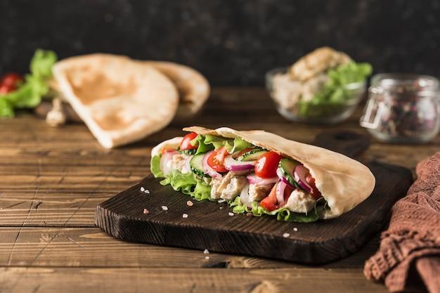Национальный греческий лаваш быстрого питания с курицей и свежими овощами на деревянной доске, темный фон, вид сбоку с копией пространства. горизонтальная ориентация.