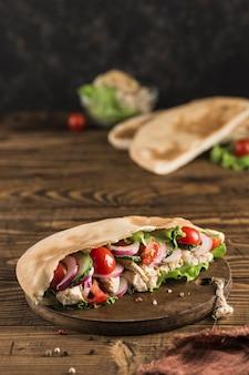 Национальный греческий лаваш быстрого питания с курицей и свежими овощами на деревянной доске, темный фон, вид сбоку с копией пространства. вертикальная ориентация.