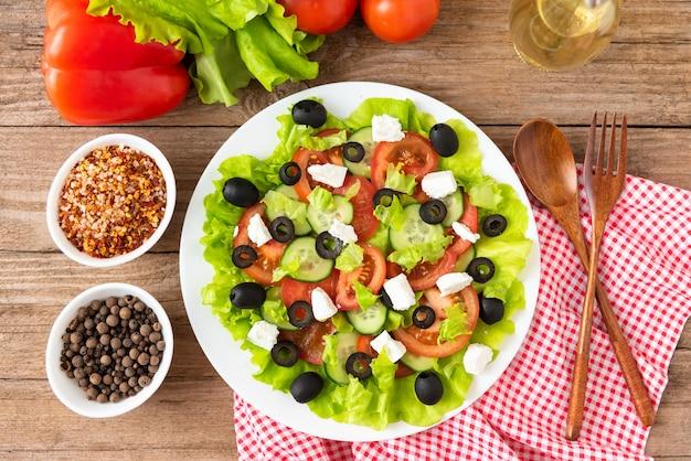木製のスペースに調味料とスパイスを添えたギリシャ風サラダ。