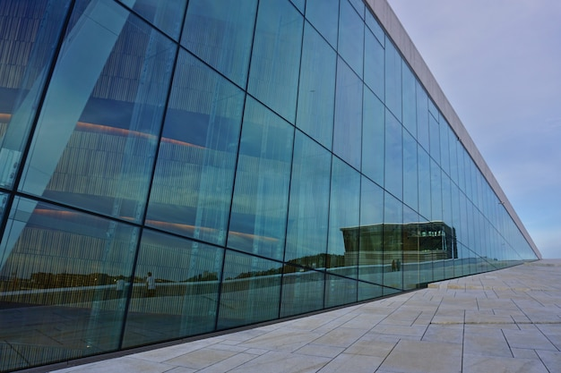 National oslo opera house against blue sky, norway. detail of the glass facade of the building.