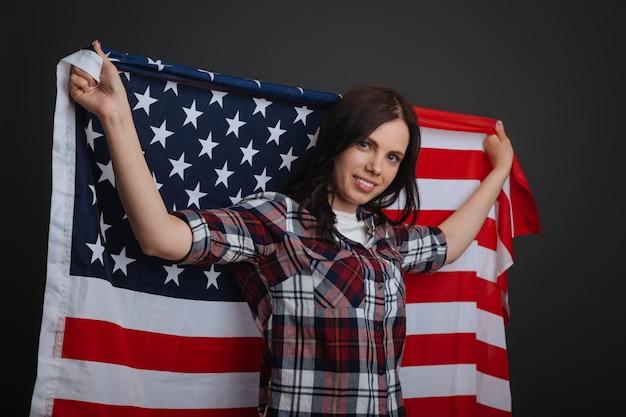 国家威信。灰色の背景に孤立して立って誇らしげに見えながら愛国的な写真撮影をする立派な魅惑的なインスピレーションを得た女の子