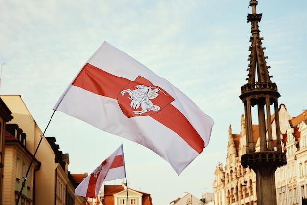 街の通りで手を振っているベラルーシの全国赤白赤旗