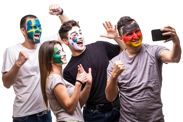 National teams painted flag face of germany, mexico, korea republic, sweden take selfie from phone.