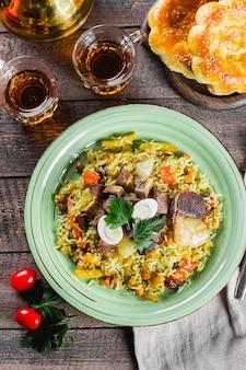 肉と木製のテーブルにご飯と国立伝統的なウズベキスタンのピラフ。東洋料理のコンセプトです。クローズアップ、トップビュー画像